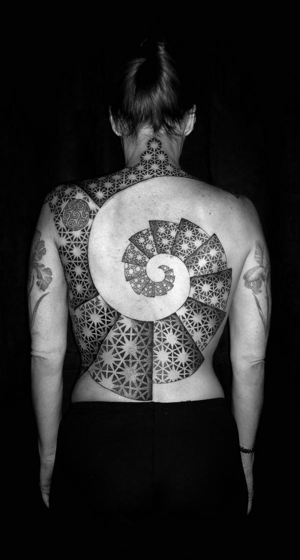 This geometric back tattoo by Tomas Tomas is using the Fibonacci spiral.