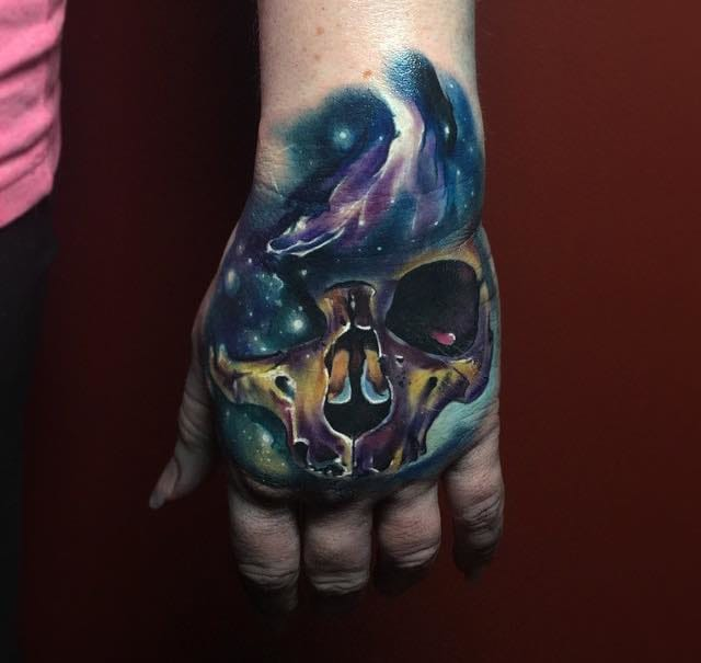 Cosmic skull hand tattoo by TJ Schunemann.