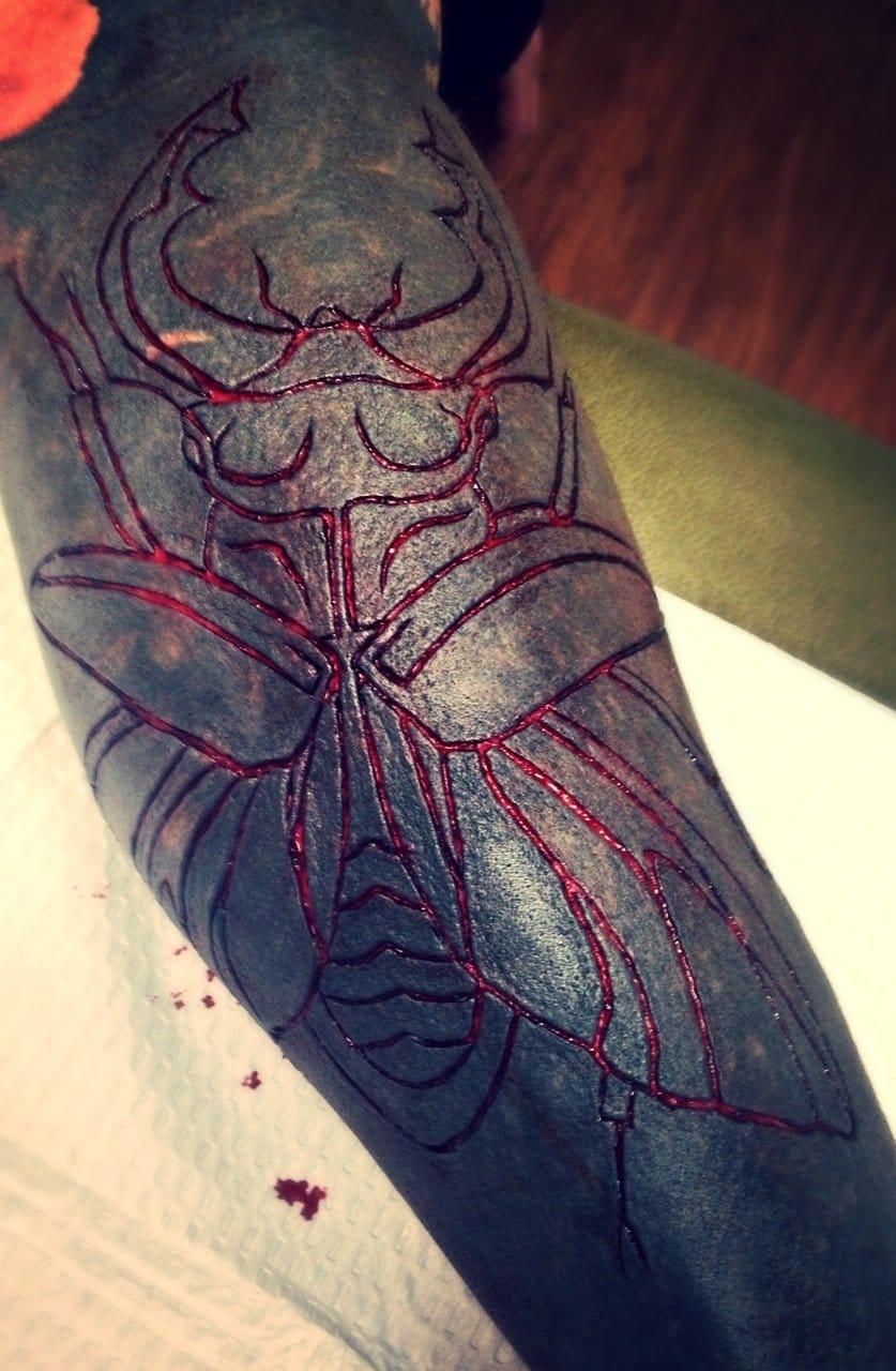 Scarification on black tattoo