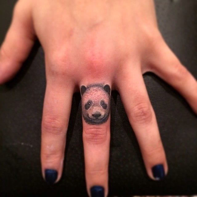 Very small panda finger tattoo by Jon Mesa.