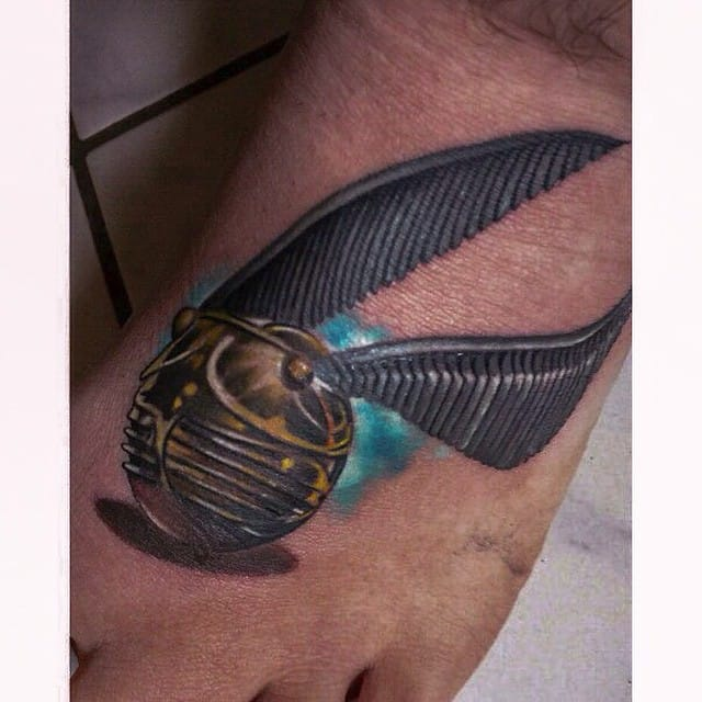 Den Hor tattooed a realistic Golden Snitch on the foot of his client. #HarryPotter #tribute #fantattoo #GoldenSnitch #realism #realistic