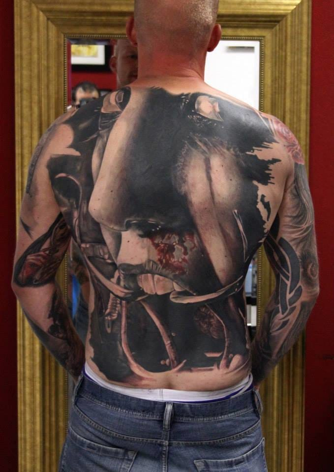 Horror tattoos like this nerve-racking backpiece are scary! Tattoo by Roberto da Silva! #horrortattoo #horror #bloody #RobertodaSilva