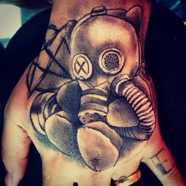 Tatuagem na minha mão esquerda de um ursinho com máscara de gás, e um pentagrama invertido atrás. Feito pelo tatuador Danial Amaral, do Black Drawing em Cascadura