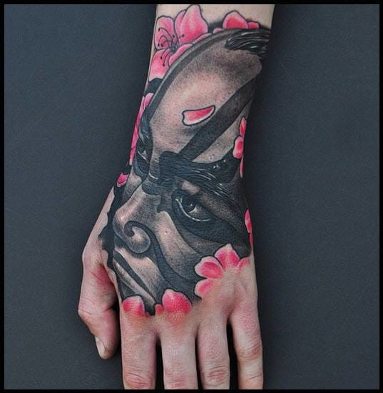 Great kabuki tattoo on the hand by Mike DeVries.