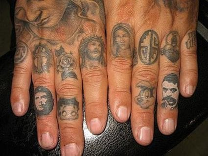 Tiny portrait tattoos on the fingers.