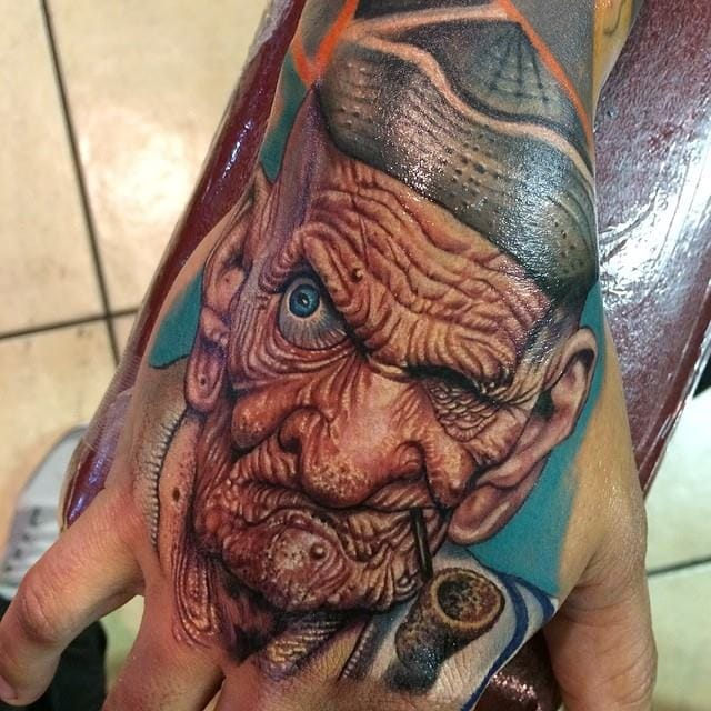 Bold hand tattoo by Roman Abrego.