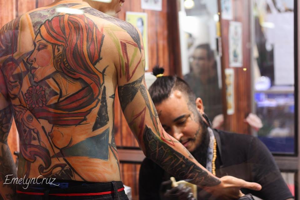 The artist André Cruz working at a tattoo convention.