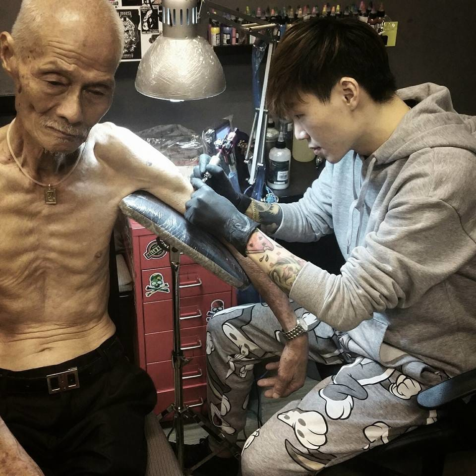 Alan Q Zhi Lun tattooing the old man, photo by Benjamin Fly