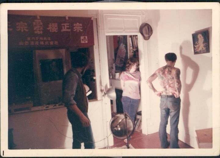 A photo of Malone and Shanghai Kate taking a picture of De Vita's tattoos in the 70's.