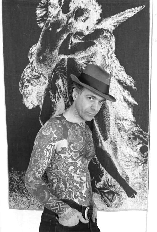 A portrait of Thom De Vita showing off his tattoos