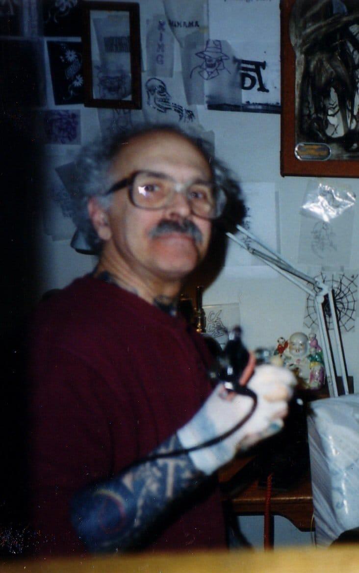 A photo of De Vita, tattooing in his studio.