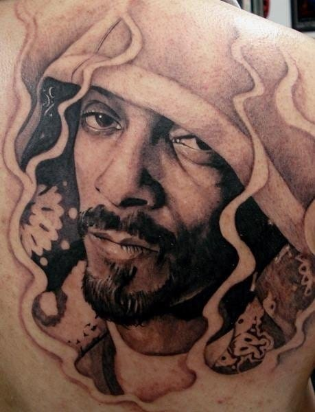 Black and gray tattoo with Snoop Dogg wearing a hood.
