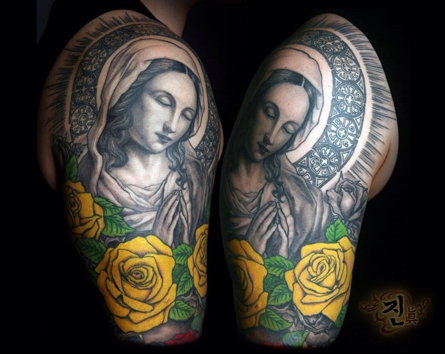 Beautiful combination of a black and gray tattoo of The Virgin Mary with colored yellow roses.