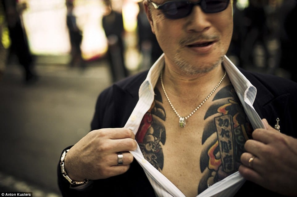 Yakuza member giving a glimpse of his tattoos.