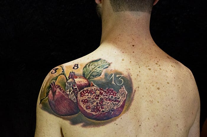 Tastefully realistic pomegranate tattoo by Lorenzo Evil Machines