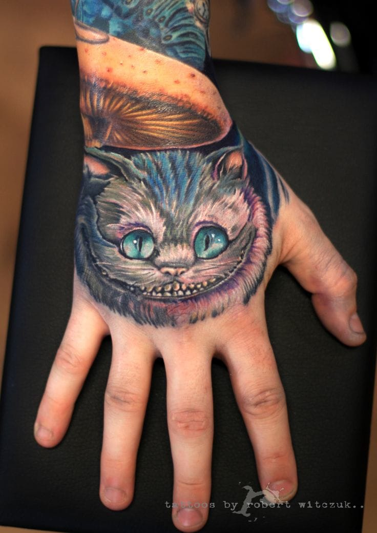 Cheshire cat on the hand by Robert Witczuk.