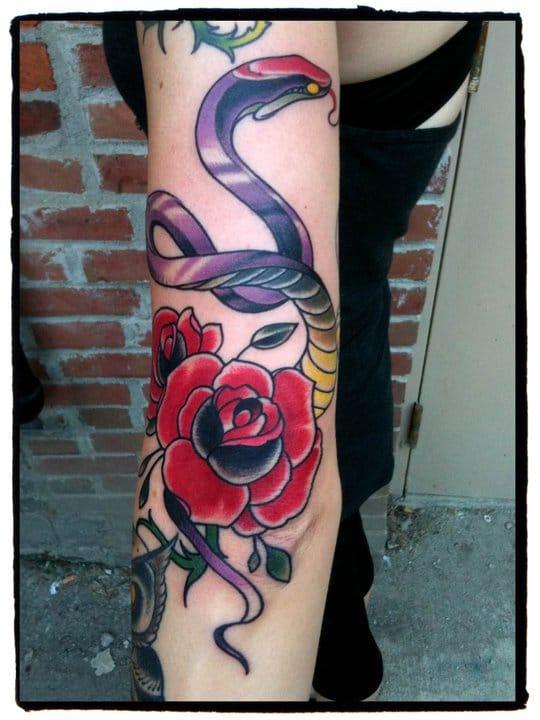 Colorful snake rose artwork on the upper arm