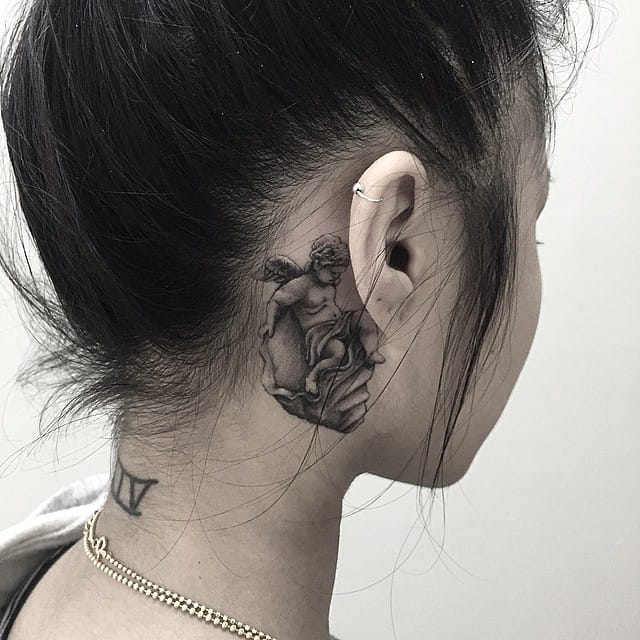 Lovely tattoo behind the ear by Eddie Lee.