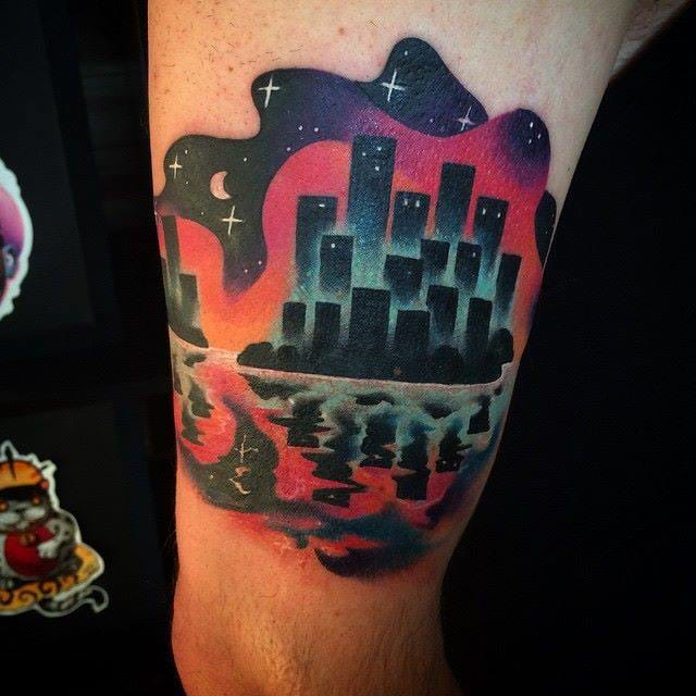 A surreal cityscape tattoo with an unreal reflection in the water below! By Giena Todryk.