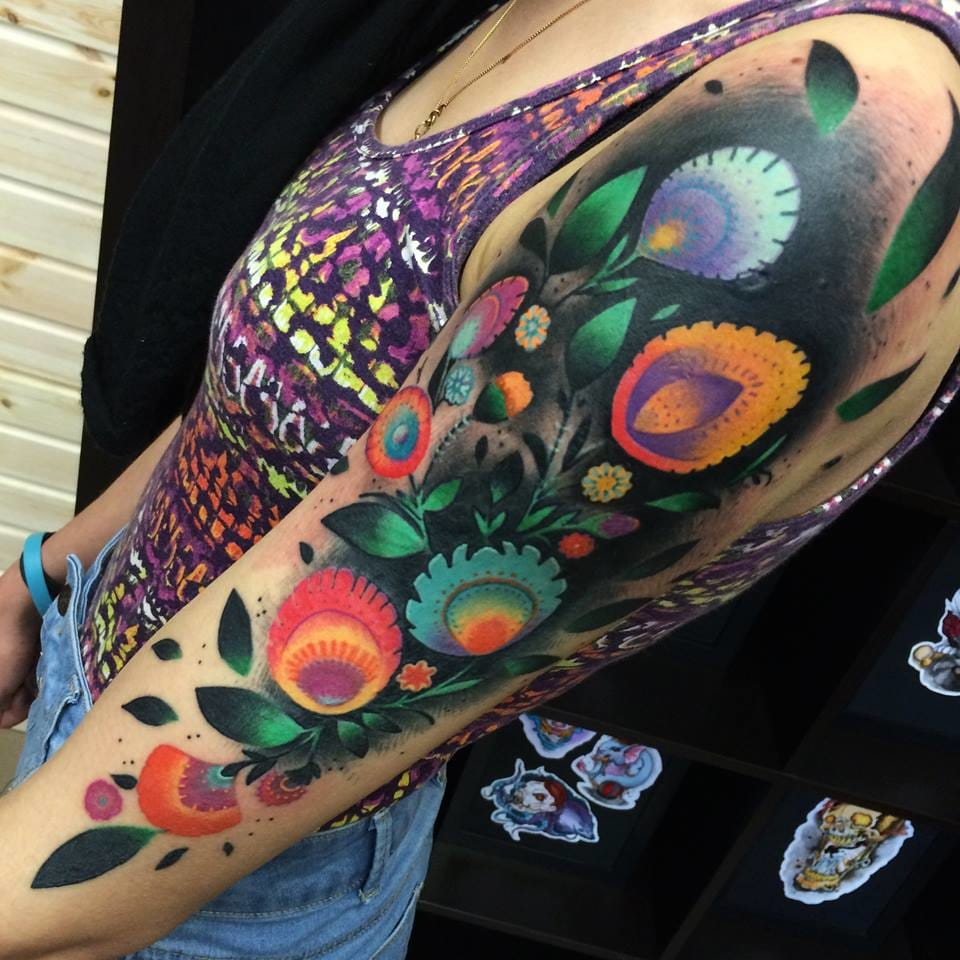 This flower tattoo sleeve by Giena Todryk is just perfect. With a varied mix of colours and background depth, these shapes fit perfectly on the arm.