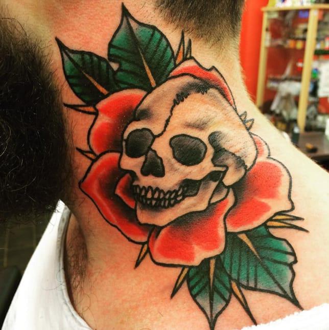 Traditional rose and skull neck tattoo ny Zombunny Tattoo. Photo from Instagram @zombunny_tattoo.