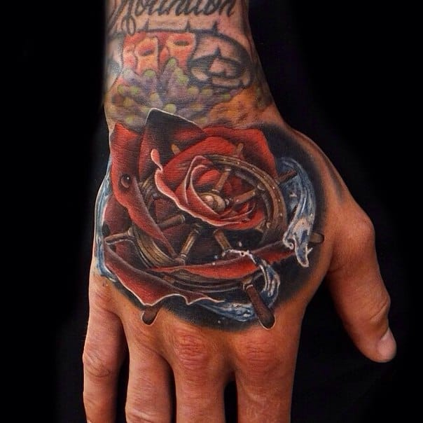 Badass hand tattoo by Andres Acosta! Even if roses are associated with feminity and love, men can ink them too to pay a tribute to a loved one or for a more intimate meaning. Get rid of clichés!