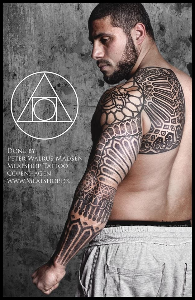 The intricate neo tribal work of Peter Walrus Madsen perfectly adorns the muscles.