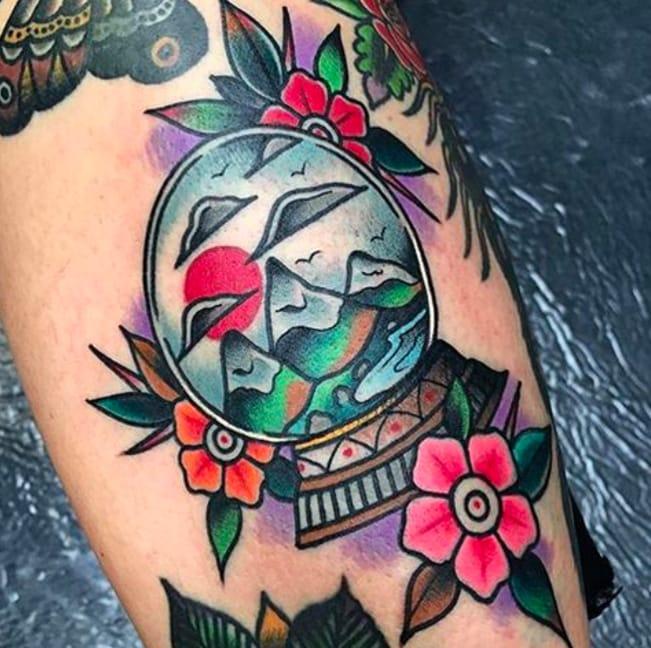 Very colourful snow globe tattoo by Instagram @pablo_de_tattoolifestyle.