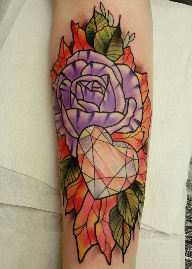 Gorgeous shading in this heart and flowers tattoo.