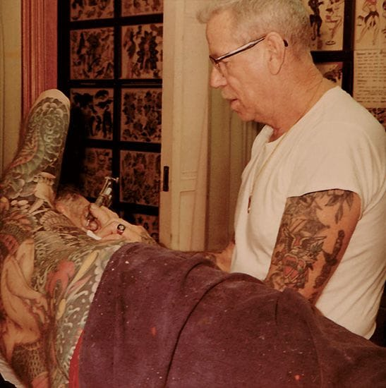 Jerry at work tattoing a man's hip