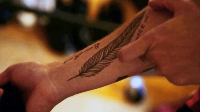 "The feather tattoo with the writings ""I figured it out"""