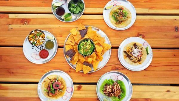 A delightful spread of tacos, house guacamole and mexican corn.