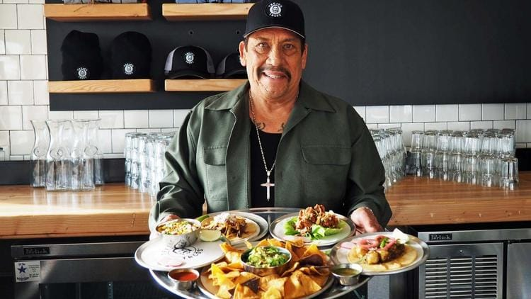 Danny Trejo, actor and proud owner of Trejo's Tacos carries a tray of some of the restaurants favorite dishes.