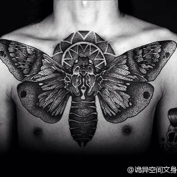 Brutal looking black moth chest tattoo!