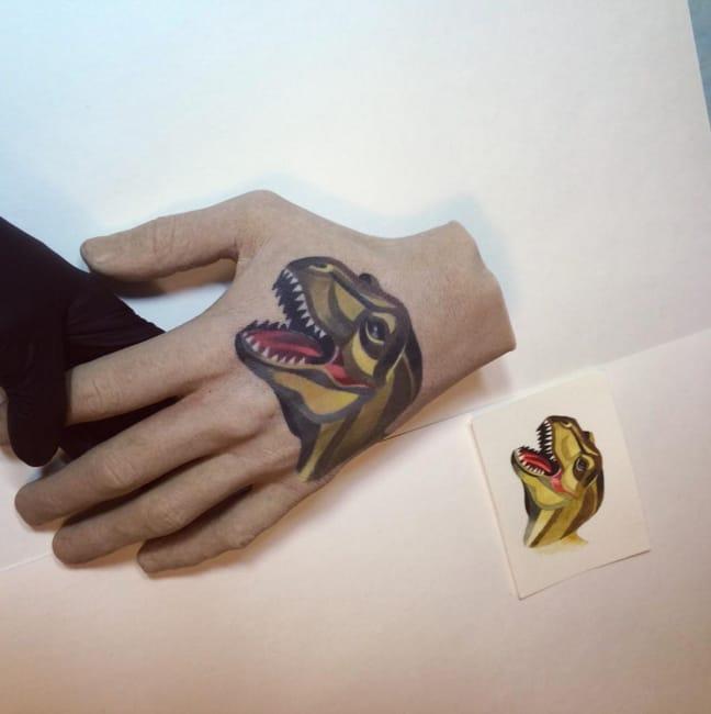 Dinosaur hand tattoo by Sasha Unisex.