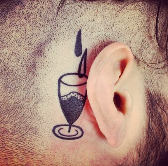 Behind the ear wine glass tattoo by Paul Hill. Photo: Instagram.