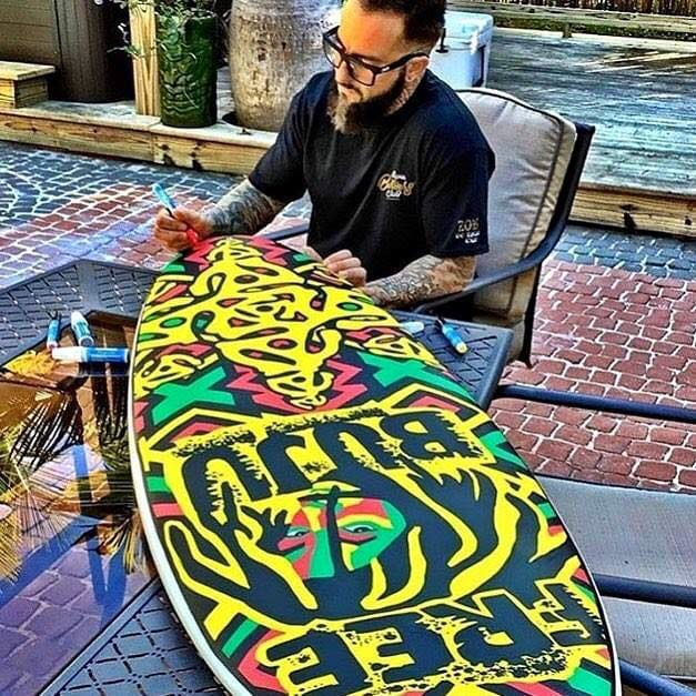 Hand painting a Reggae-themed surfboard.