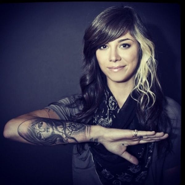 Christina Perri wearing her forearm tattoo of 'My Dishonest heart' a painting by Audrey Kawasaki.
