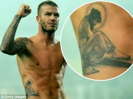 Athlete David Beckham celebrating his tattoo of Jesus on the ribs.