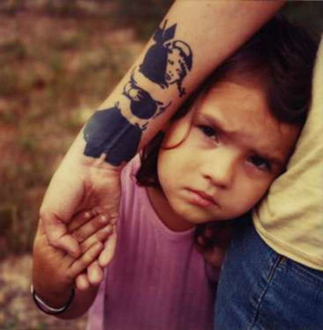 The Girl with a bomb tattoo and this little girl are making a strong photo, by Mike Brodie.
