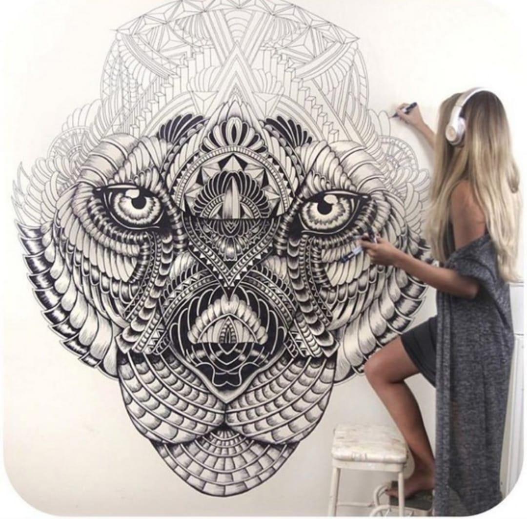 Faye Halliday gets down to business on a Lion wall mural. Instagram @fayehallidayart