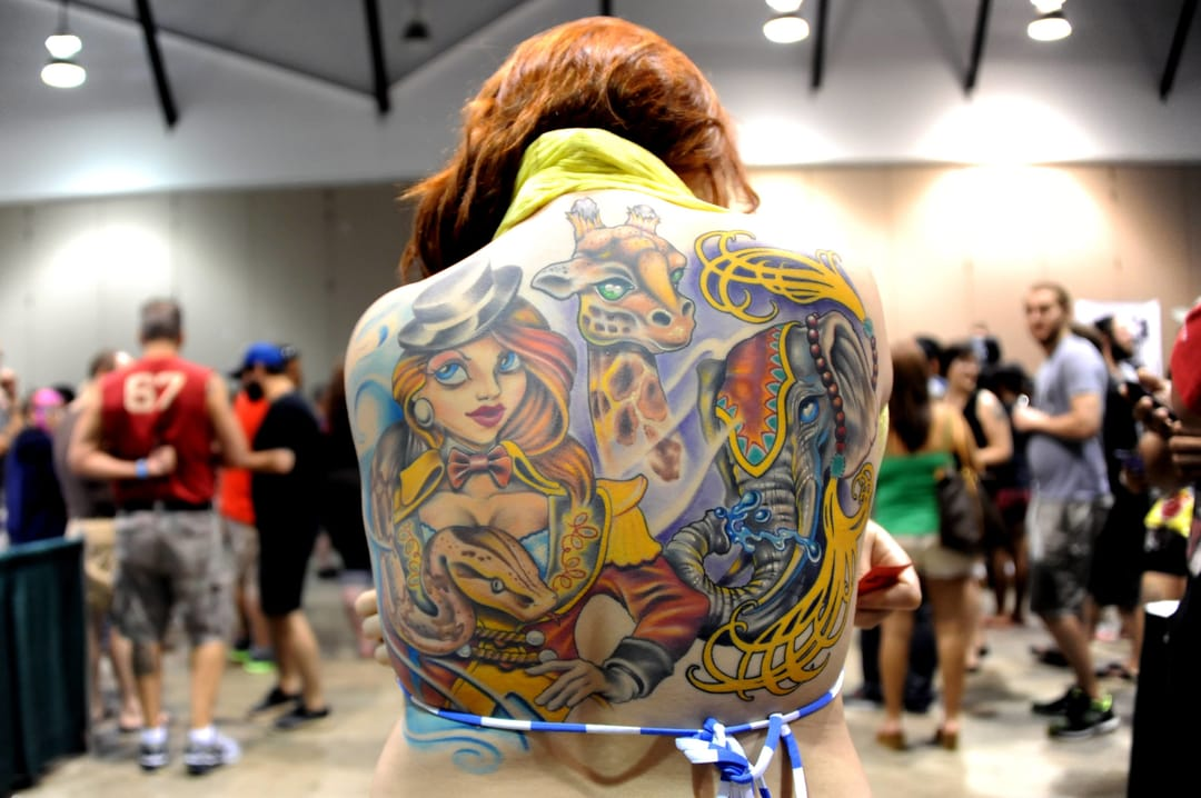 New school backpiece shot by Alexandra Olivia at a tattoo convention.