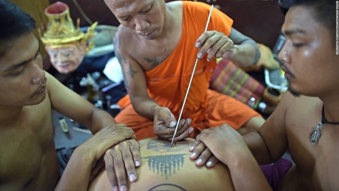 A monk performing a Yantra tattoo, via CNN