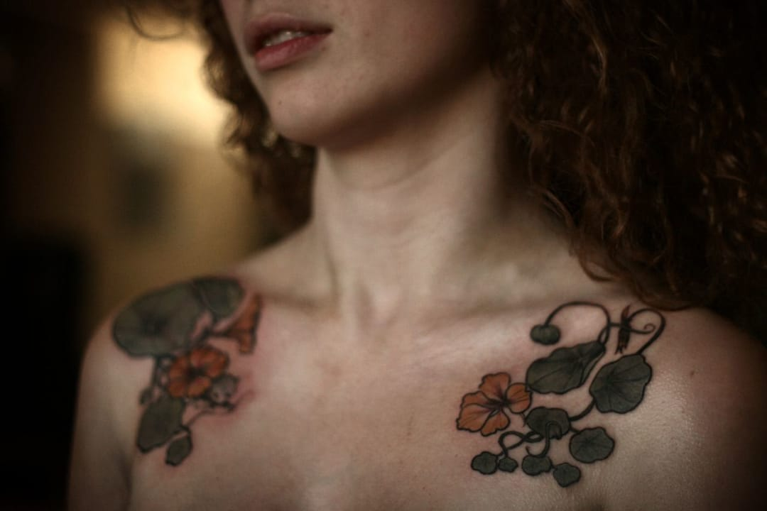 Nasturtium flower on shoulders by Alice Carrier.