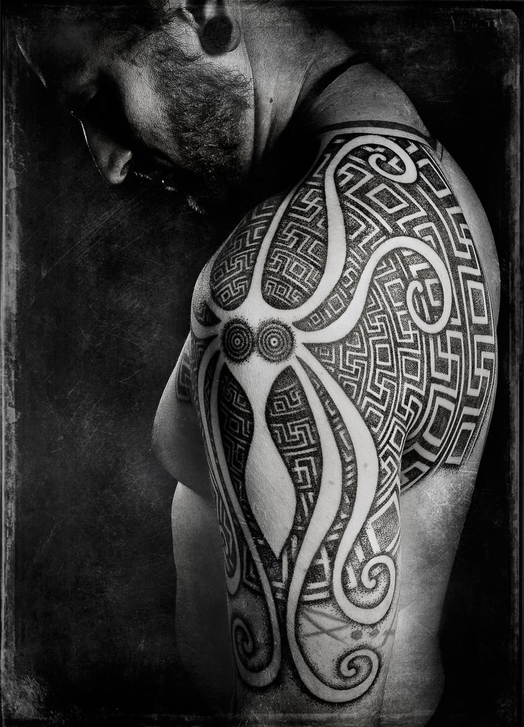 Negative space octopus in this neo tribal shoulder tattoo by Peter Blackhand Madsen.